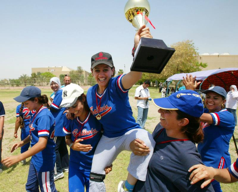 A female softball player, her teammates, a trophy