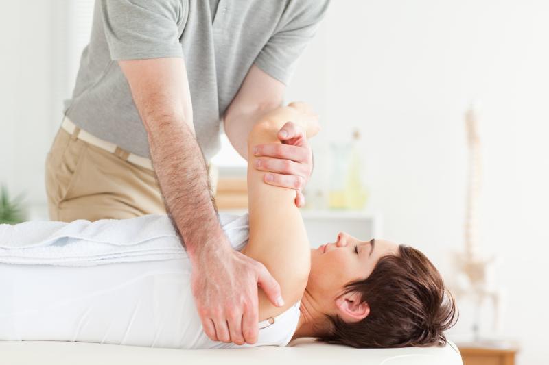 A therapist, a patient's shoulder